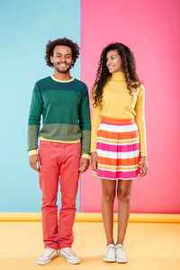 Full length of happy african american young couple standing and smiling over colorful background