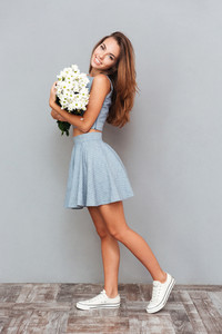 Full length of happy cute young woman standing and holding bouquet of flowers over grey background
