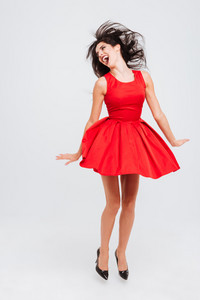 Full length of happy excited young woman in red dress laughing and jumping in the air over white background