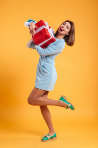 Full length of happy funny young woman with present box eating lollipop over yellow background