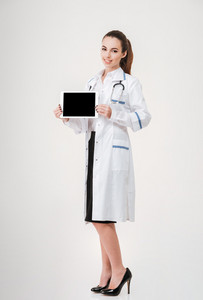 Full length of happy young woman doctor standing and holding blank screen tablet