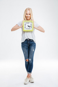 Full length of happy young woman standing and holding clock isolated on a white background