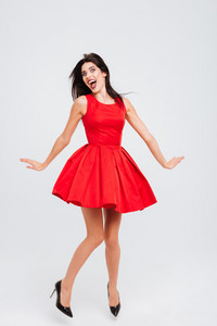 Full length of joyful cute young woman in red dress dancing and having fun over white background