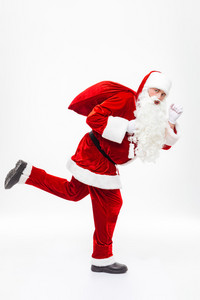 Full length of man santa claus holding gift sack and running