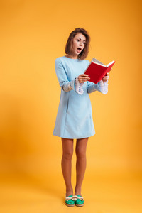 Full length of pretty astonished young woman standing and reading book over yellow background