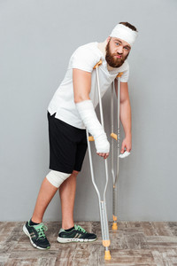 Full length of sad tired young man walking with crutches over white background