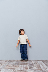 Full length of scared little boy standing over gray background