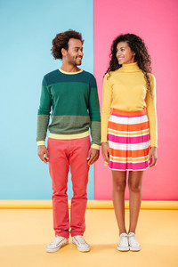 Full length of smiling african young couple standing and looking at each other over colorful background
