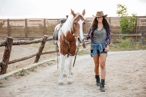 Full length of smiling beautiful young woman cowgirl walking with horse