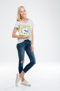 Full length of smiling beautiful young woman standing and holding clock isolated on a white background