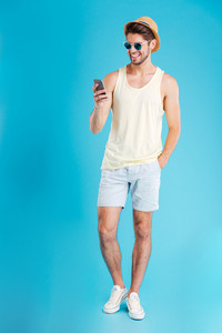 Full length of smiling cute young man standing and using mobile phone over blue background