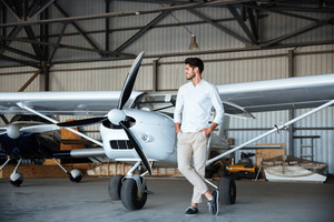 Full length of smiling young man standing near small aircraft