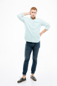 Full length of thoughtful young man standing and thinking over white background