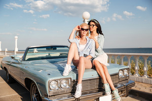Full length of two attractive young women sitting on car