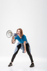 Full length portrait of a angry young girl standing and screaming in megaphone isolated on a white background