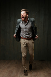 Full length portrait of a bearded young man in jacket posing and screaming isolated on a black wooden background