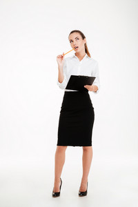 Full length portrait of a beautiful pensive businesswoman holding clipboard and looking up isolated on white background