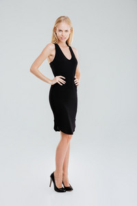 Full length portrait of a beautiful serious woman posing in black dress with hands on hips isolated on a white background