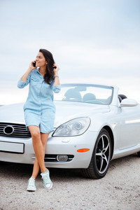 Full length portrait of a beautiful young woman talking on smartphone and standing at her car