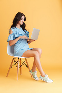 Full length portrait of a brunette smiling woman working on laptop while sitting on chair isolated on the orange background