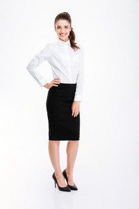Full length portrait of a businesswoman standing with hand on hip isolated on a white background
