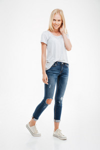 Full length portrait of a casual attractive blonde woman standing isolated on a white background