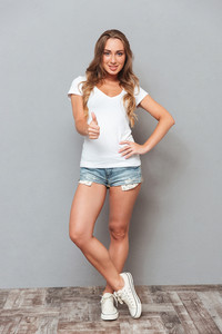 Full length portrait of a casual attractive woman standing and showing thumbs up gesture isolated on a gray background