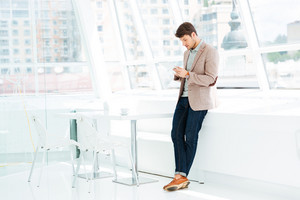 Full length portrait of a casual businessman standing and using mobile phone indoors