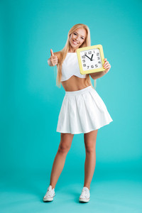 Full length portrait of a casual smiling girl holding wall clock and showing thumbs up gesture isolated on the blue background
