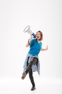 Full length portrait of a casual young girl shouting into loudspeaker isolated on a white background