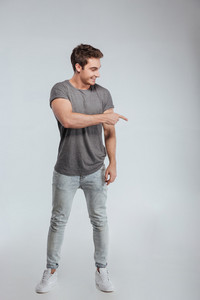 Full length portrait of a casual young man standing and pointing finger down isolated on a white background