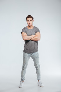 Full length portrait of a casual young man standing with arms crossed and looking at camera isolated on the gray background