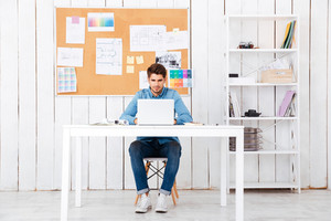 Full length portrait of a casual young man with laptop sitting at desk at the office