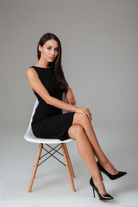 Full length portrait of a charming brunette businesswoman in black dress sitting on chair over gray background