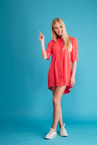 Full length portrait of a cheerful blonde girl in red dress standing and pointing finger up isolated on the blue background