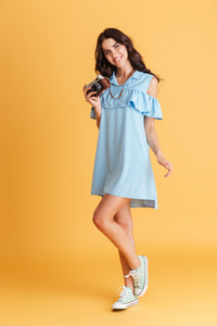 Full length portrait of a cheerful brunette in blue dress holding retro camera isolated on a orange background