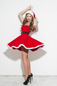 Full length portrait of a cheerful happy woman in red christmas costume having fun isolated over white background