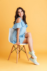 Full length portrait of a cheerful smiling woman in blue dress sitting on chair isolated on a orange background