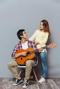 Full length portrait of a cheerful young couple resting with guitar isolated on the gray background