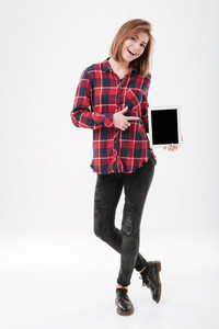 Full length portrait of a cheerful young girl in plaid shirt holding and pointing finger on blank screen tablet over white background