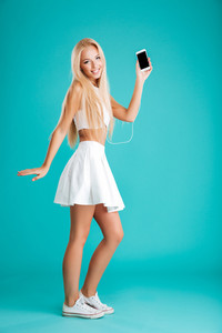 Full length portrait of a cheerful young woman holding blank screen mobile phone and listening music with earphones isolated on the blue background