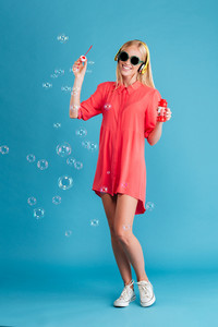 Full length portrait of a cheerful young woman in sunglasses blowing soap bubbles and listening music with headphones over blue background