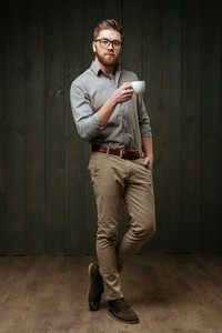 Full length portrait of a concentrated bearded man in eyeglasses standing and holding cup of coffee isolated on a black wooden background