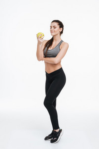 Full length portrait of a confident focused sports woman standing and looking at apple in her hand isolated on a white background