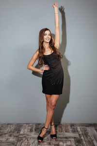 Full length portrait of a fashion happy woman posing in black dress isolated on a grey background