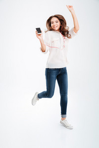 Full length portrait of a funny woman listening music and jumping over white background