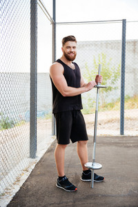 Full length portrait of a handsome young smiling fitness man holding barbell outdoors