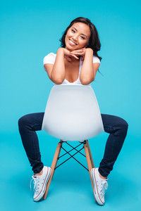 Full length portrait of a happy attractive asian woman sitting on the chair isolated on a blue background