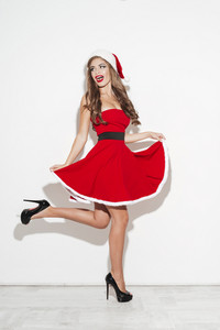 Full length portrait of a happy attractive young woman having fun in red santa claus costume isolated over white background