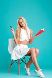 Full length portrait of a happy blonde woman holing notebook and sitting on chair isolated on the blue background